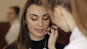 Young girl does make-up woman in beauty salon. stock footage