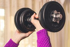 A young girl does sports, she lifted a heavy dumbbell_ stock photography