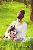 Young girl with a dog Husky spring Stock Image