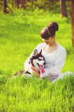 Young girl with a dog Husky spring Royalty Free Stock Photos