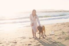Young Girl and Dog Walking along the Seashore Royalty Free Stock Image