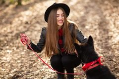 Young girl with a dog walking in the autumn park. Girl has a beautiful black hat royalty free stock photography