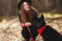 Young girl with a dog walking in the autumn park. Girl has a beautiful black hat stock photo