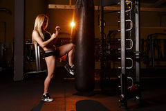 Young girl doing boxing workout in the gym. Female fighter kicking punching bag. Royalty Free Stock Photos