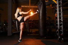 Young girl doing boxing workout in the gym. Female fighter kicking punching bag. Royalty Free Stock Images