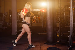 Young girl doing boxing workout in the gym. Female fighter smash punching bag. Royalty Free Stock Photos