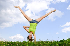 Young girl doing cartwheel Royalty Free Stock Photos