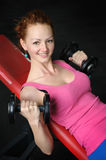 Young girl doing Dumbbell Incline Bench Press workout. In gym Stock Photography