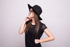 Young girl doing emotion. Dressed in a black shirt, black hat, glasses in studio Royalty Free Stock Image