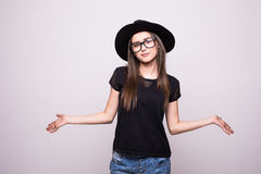 Young girl doing emotion. Dressed in a black shirt, black hat, glasses. Royalty Free Stock Photo