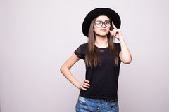 Young girl doing emotion. Dressed in a black shirt, black hat, glasses in studio Stock Photos