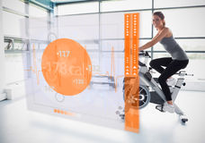 Young girl doing exercise bike with futuristic interface showing calories Royalty Free Stock Photography