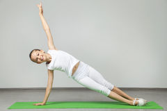 Girl doing exercises. Young girl doing exercises on green yoga mat Royalty Free Stock Images