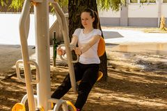 Young girl doing exercises outdoor on sunny day Stock Image