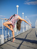 Young girl doing gymnastic exercises on the pier (normal ver) Royalty Free Stock Image