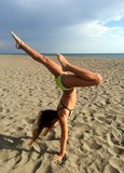 Young girl doing handstand exercize on the beach stock image