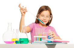 Young girl doing her chemical test in laboratory. Young girl dripping from a pipette some blue reactant from the flask at the  laboratory Royalty Free Stock Photos