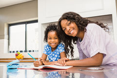 Young girl doing her homework with her mother Royalty Free Stock Images
