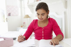 Young Girl Doing Homework At Desk In Bedroom Stock Image