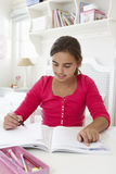Young Girl Doing Homework At Desk In Bedroom Royalty Free Stock Images