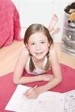 Young Girl Doing Homework On Floor Royalty Free Stock Photo