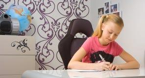 Young girl doing homework at home Stock Image