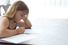 Young Girl Doing Homework at Kitchen Table Stock Image