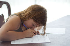 Young Girl Doing Homework at Kitchen Table Royalty Free Stock Photos