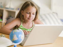Young Girl Doing Homework On A Laptop.  royalty free stock images