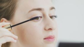 Young girl doing makeup of eyes by black mascara, looking at mirror. 4K stock video