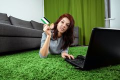 Young girl doing online shopping while sitting at home. The concept of online shopping, shopping online store, home delivery stock photography