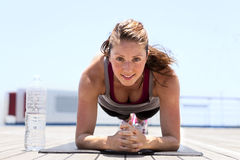 Young girl doing plank. Beautiful young girl working out on a sunny day Stock Image