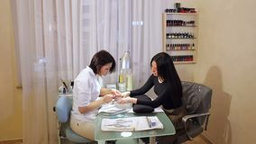 Manicurist makes manicure for a young woman. Nail care. A young girl doing a professional manicure in a beauty salon. Manicurist makes manicure for a young stock footage