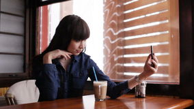 Young girl doing selfie on smartphone in the cafe stock video footage