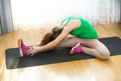 Young girl doing sport exercise on yoga mat at home Royalty Free Stock Image