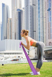 Young girl doing sports in Dubai city. Pretty young fit girl is doing sports with rubber band in a modern urbanistic city against modern skyscrapers in Dubai Royalty Free Stock Images