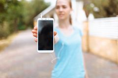 Young girl doing sports on the street, shows the phone with an isolated place. Young girl, doing sports on the street, shows the phone with an isolated place Royalty Free Stock Images