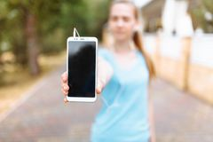 Young girl doing sports on the street, shows the phone with an place. Young girl, doing sports on the street, shows the phone with an place Royalty Free Stock Photos