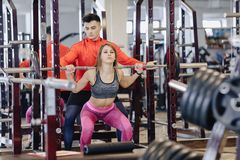 Young girl doing squats with a barbell in the gym under the supervision of a trainer royalty free stock images