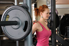 Young girl doing squats with barbell Stock Images