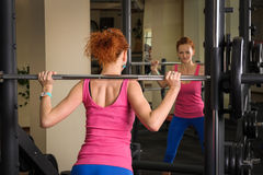 Young girl doing squats with barbell Stock Photo
