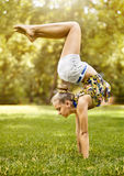 Young girl doing stretching exercise on green Royalty Free Stock Photography