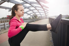 Young girl doing stretching exercises on the bridge. Young woman doing stretching exercises on the bridge after jogging at the sunset Royalty Free Stock Photos