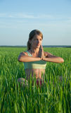 Young girl doing yoga against nature. Beautiful young girl practicing yoga  against blue sky Stock Photography