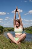 Young girl doing yoga against nature Stock Photography