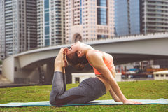 Young girl doing yoga against skyscrapers Stock Image