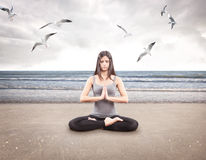 Young girl doing yoga on the beach royalty free stock photography