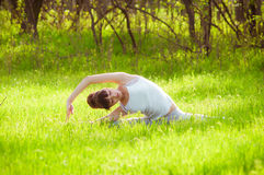 Young girl doing yoga on a green grass Royalty Free Stock Images