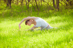 Young girl doing yoga on a green grass Royalty Free Stock Image
