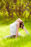 Young girl doing yoga on a green grass Royalty Free Stock Photo